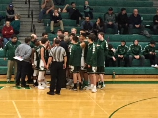 Boys Basketball players  about leave the huddle after a timeout.